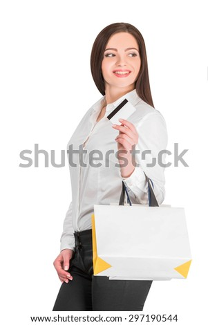 Young attractive woman with shopping bags and credit card on a white background - stock photo