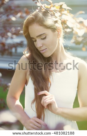 Young attractive woman with the long hair enjoying morning in the park