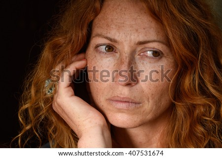 young attractive woman without makeup with long curly red hair holding hand on her chin looking away and thinking about problems close up - stock photo