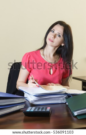 Young attractive woman working with documents in the workplace in the office