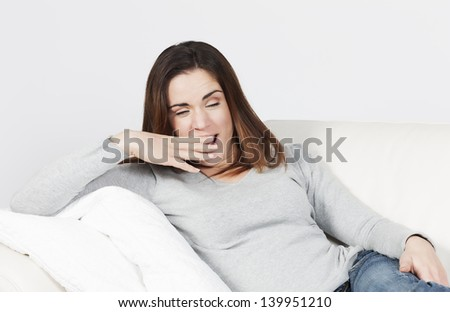young attractive woman yawning on sofa - stock photo