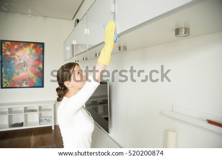 Young attractive young woman cleaning an upper surface of the shelf wearing rubber protective yellow gloves, with a rag. Home, housekeeping concept