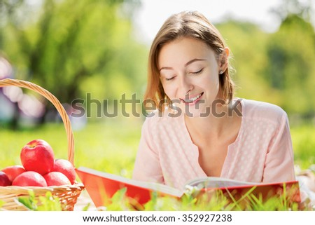 Young attravctive woman in summer park having picnic - stock photo
