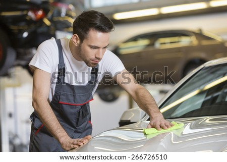 Young automobile mechanic cleaning car in repair shop - stock photo
