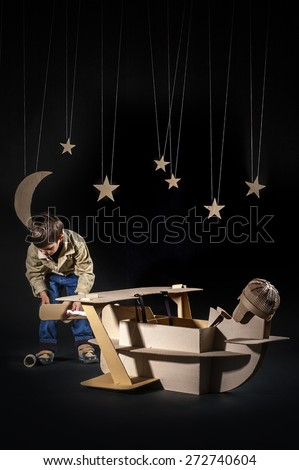 Young aviator assembling corrugated plane on the dark night sky background