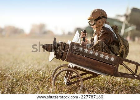 Young Aviator sits in his makeshift toy airplane on airport parking - stock photo