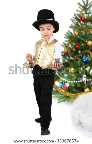 Young baby boy looking at a christmas decorative toys during christmas tree decoration. Holiday and family concept. New year and christmas eve atmosphere. - stock photo