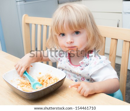 Young baby feeding herself in the family home. - stock photo