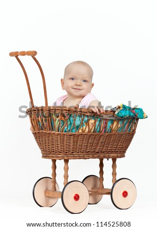 Young baby girl in a wicker pram