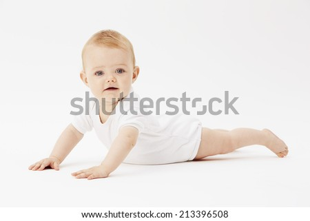 Young baby girl looking down, studio  - stock photo