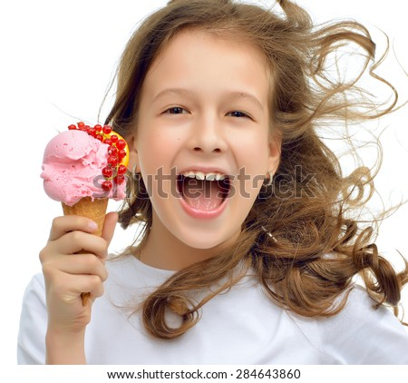 Young baby girl ready for eating red strawberry ice cream in waffles cone with orange and fruits isolated on a white background - stock photo