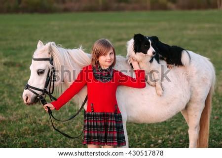 Young baby girl. Red dress. Dog on horseback. Little White Horse pony Outdoors - stock photo