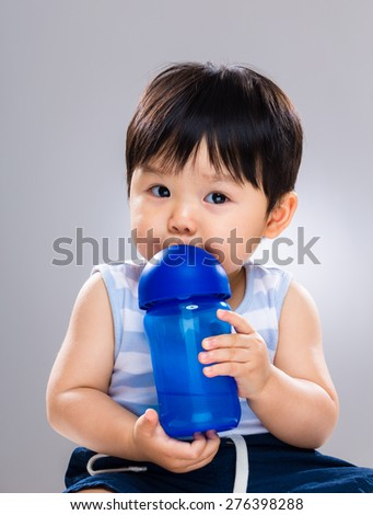 Young baby son drinking with water bottle