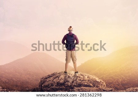 Young backpacker enjoying a valley view from top of a mountain - stock photo