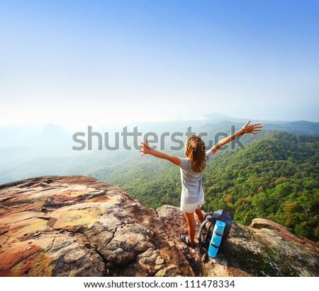 Young backpacker standing on top of a mountain and enjoying a morning valley view - stock photo