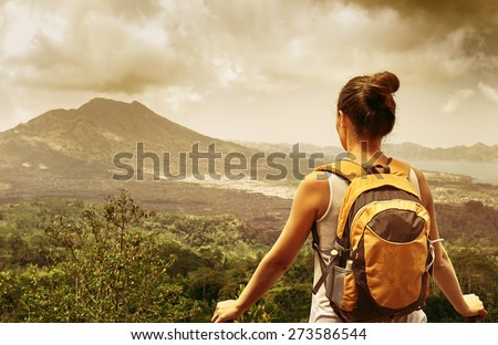 Young backpacker traveling along mountains, happy female walking in the island to Bali, discovering world, summer vacation concept - stock photo