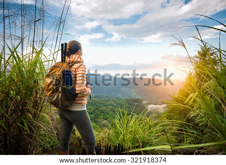 Young backpacker traveling  with backpack standing on top of the mountain and enjoying sunrise view - stock photo