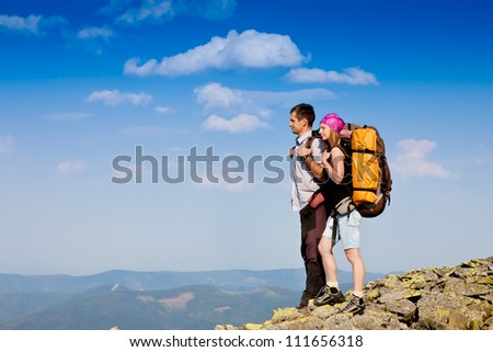 Young backpackers enjoying a valley view from top of a mountain - stock photo