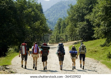 Young backpackers walking in the mountains in a summer day