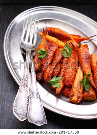 Young baked carrots on a black background
