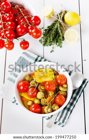 young baked potatoes with carrots, mushrooms and grilled cherry tomatoes in white plate