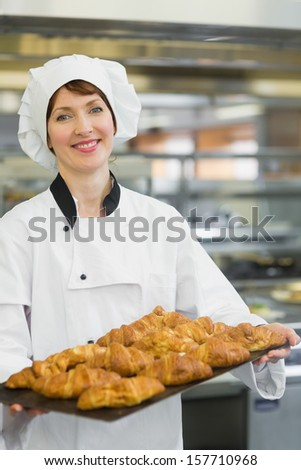 Young baker presenting croissants on a baking tray