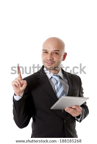 young bald latin happy smiling man wearing business suit and blue necktie  holding a tablet pointing with hand finger to white background copy space for adding text message , logo or advertising