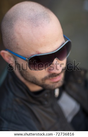 Young bald man with sunglasses