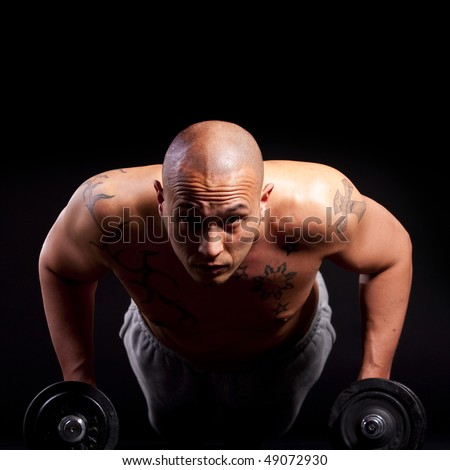 Young bald strong man is working out over black background. - stock photo