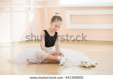 Young ballerina changing dancing shoes to pointe ones while sitting on floor - stock photo
