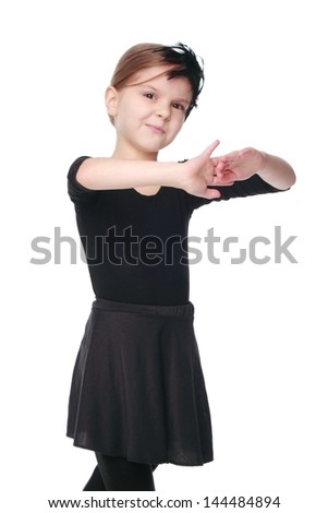 Young ballerina dancer/Smiling little ballet dancer in a black suit in a dance pose expresses the emotions of a dance - stock photo