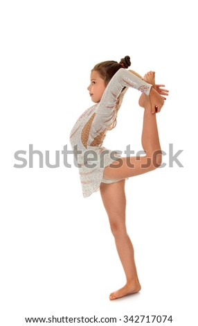 Young Ballerina dressed in sports costume performs an exercise turning the camera sideways - Isolated on white background - stock photo