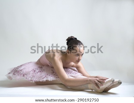 Young ballerina in a pink ballet tutu is dancing on a white background - stock photo