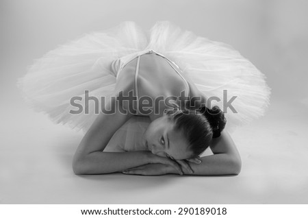 Young ballerina in white ballet tutu is dancing on a white background - stock photo