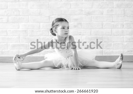 Young ballerina in white clothes sitting on the floor during the training in dance class. - stock photo