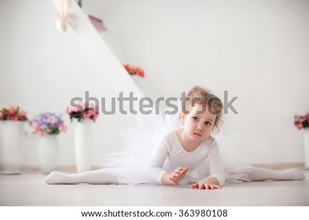Young ballerina in white clothes sitting on the floor during the training. Stretching. Girl doing gymnastic split. - stock photo