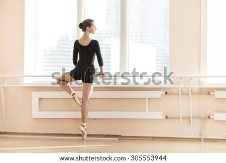 Young ballerina standing on poite at barre in ballet class  - stock photo