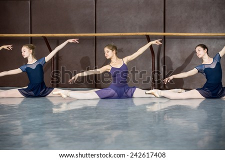 Young ballerinas on the lesson of classical choreography sitting in the splits gracefully raising his hands up near barre. - stock photo