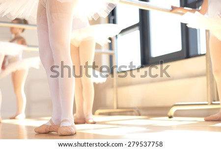 Young ballerinas wearing pointe shoes, the special reinforced satin shoes allowing a ballet dancer to stand on tip toe, low angle view of a class in progress - stock photo