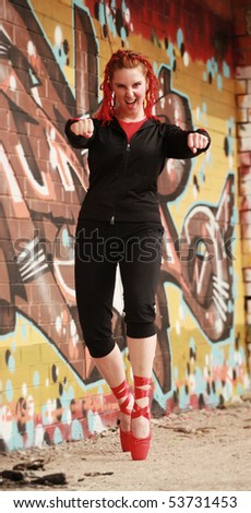 young ballet dancer posing against graffiti wall - stock photo
