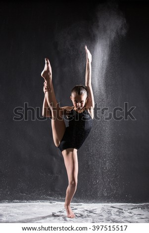 Young ballet dancer with flying powder doing the splits