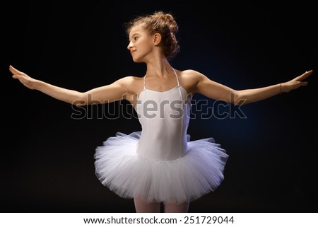 Young ballet student exercising over black background in tutu. - stock photo