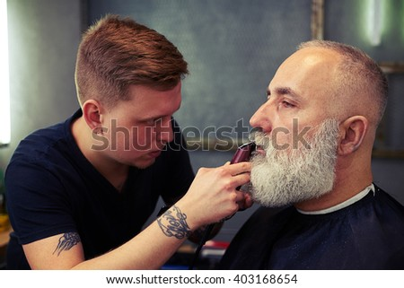 Young barber with tattoo shaving beard of his client with hair clipper in hair salon - stock photo