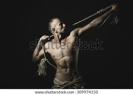 Young bare handsome boy with sexy strong muscular body with long durable rope standing on studio black background, horizontal picture