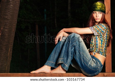 young barefoot woman in hippie style clothes, outdoor shot, full body shot - stock photo