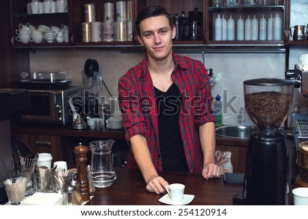 Young barista  at cofeeshop made a cup of coffee and smile charming - stock photo