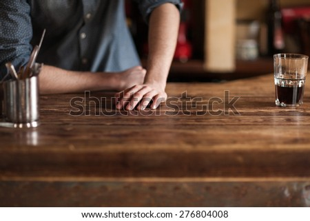 Young barman leaning on wooden bar counter hands close up, unrecognizable person - stock photo