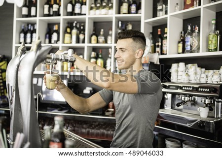 Young barman serving beer glass, waiter.