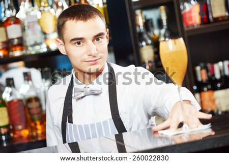 young barman worker at bartender desk serving coctail in restaurant bar  - stock photo