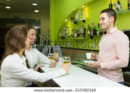 Young bartender and two beautiful girls with wine glasses in hands at bar. Focus on man - stock photo